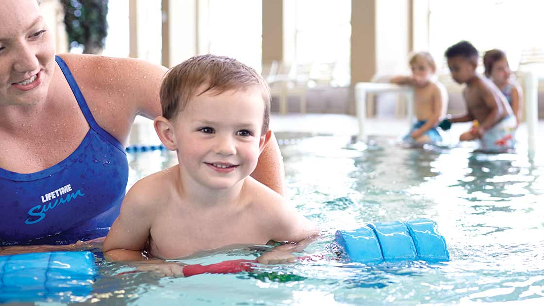 Image of a boy and a teacher at kids swimming lessons