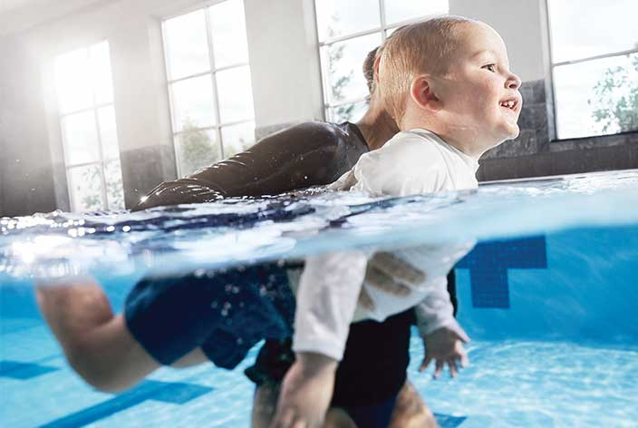 A Life Time instructor gives swimming lessons to a child in an indoor swimming poo