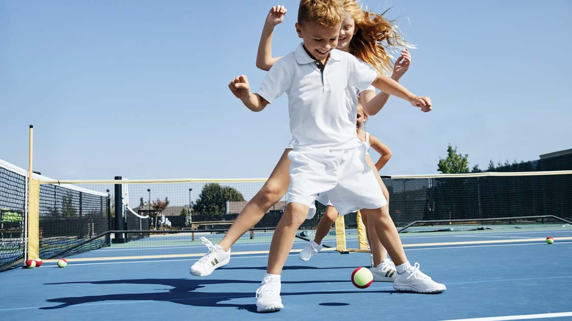 A young girl and young boy dance over a tennis ball on an outdoor tennis court