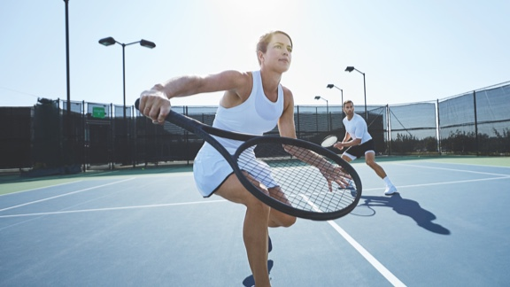A woman in a white tank top and tennis skirt steps forward on an outdoor tennis court to take a one-handed backhand swing with a tennis racquet