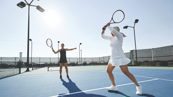 A woman in a black tennis outfit and a woman in a white tennis outfit on an outdoor tennis court raise their rackets above their heads in celebration