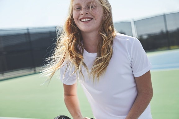 A girl with long blond hair wearing a white t shirt stands on an outdoor tennis court and smiles.