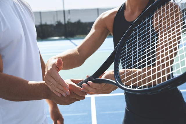 A female tennis instructor in a black tennis outfit helps a male student in a white tennis outfit perfect his grip on a tennis racquet on an outdoor tennis court