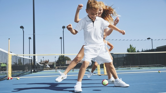 A young girl and young boy dance over a tennis ball on an outdoor tennis court.