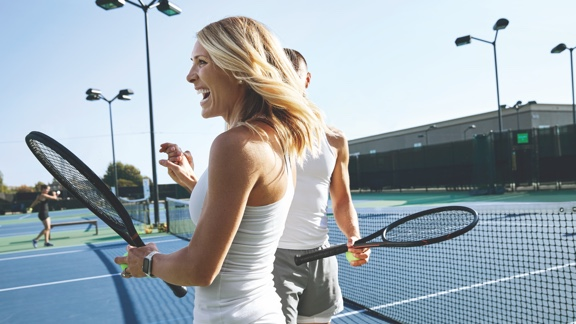 A woman in a white tennis shirt and white tennis skirt and a man in a white tennis shirt and gray tennis shorts hold racquets and laugh on an outdoor court