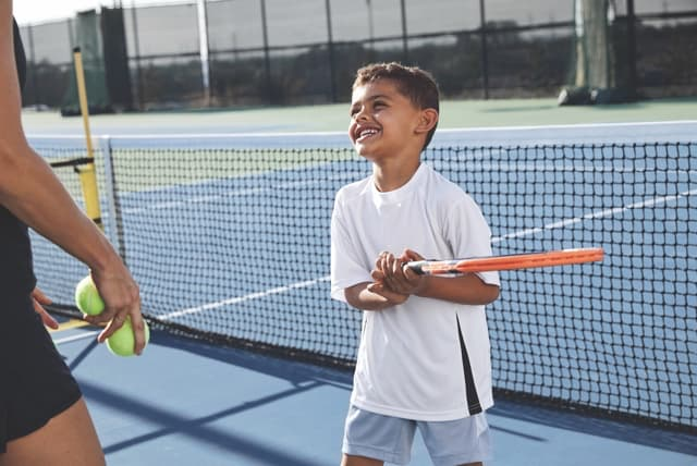 A young boy in a white t-shirt and gray shorts holds a tennis racquet and smiles at an adult tennis coach in black tennis shorts who is holding two tennis balls in one hand.