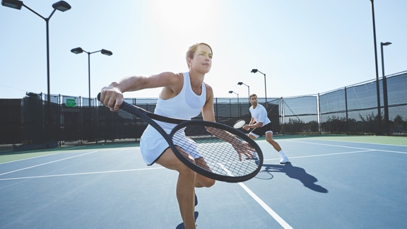A woman in a white tennis outfit takes a one-handed backhand swing with a tennis racquet on an outdoor tennis court