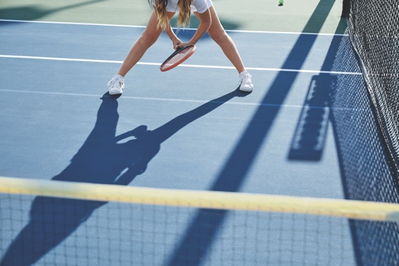 A girl in white tennis shorts stands in the ready position and holds a tennis racquet on an outdoor tennis court.