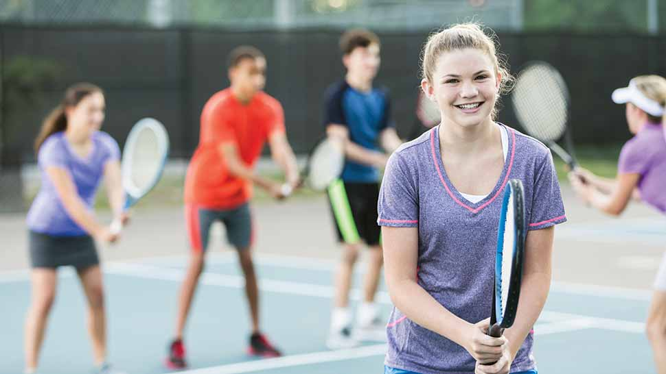 Image of a smiling teen girl at a tennis class