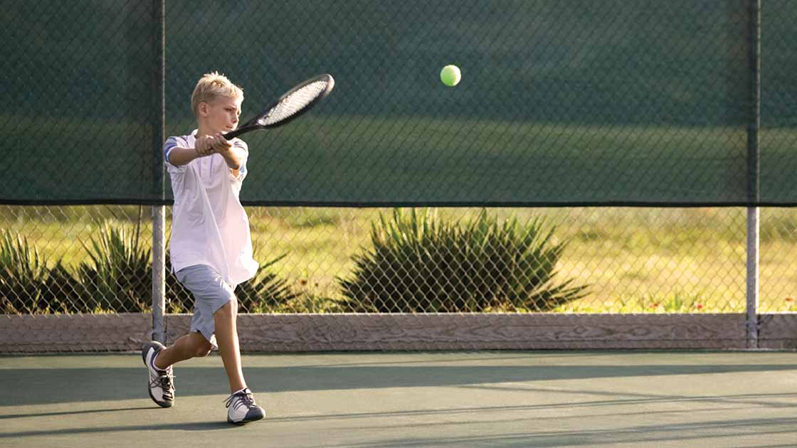 Image of a teen boy swinging a tennis racket at a ball