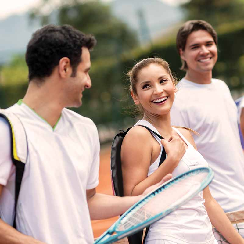 image of three adults on a tennis court