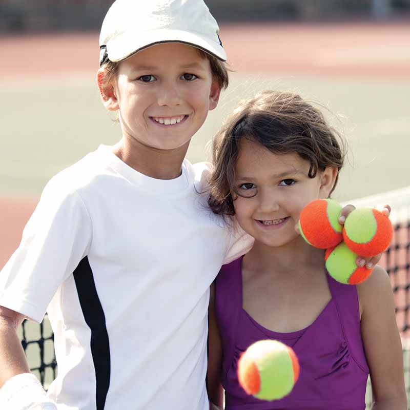 Image of two kids smiling and holding tennis balls