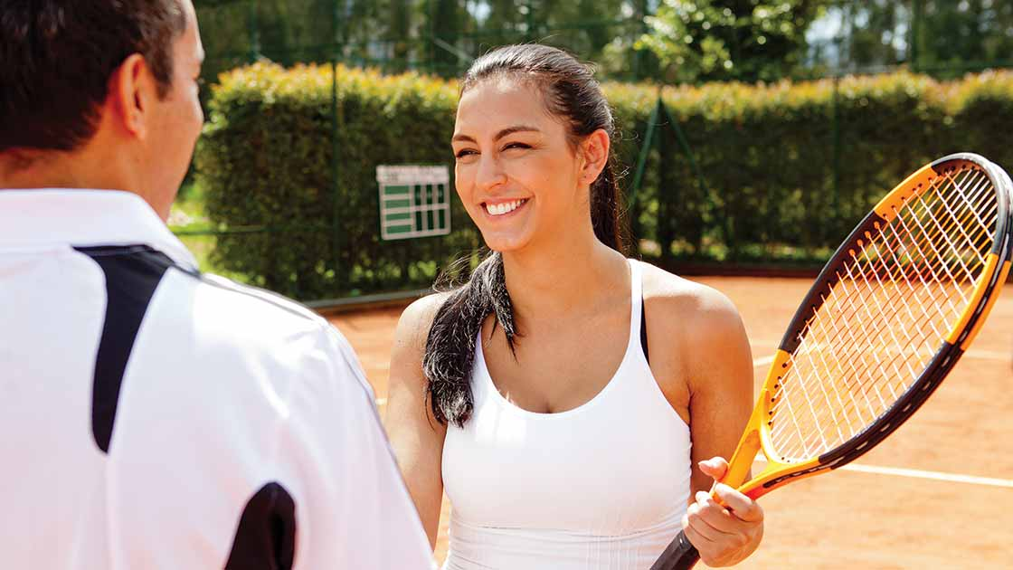 Image of two adults smiling and talking on a tennis court