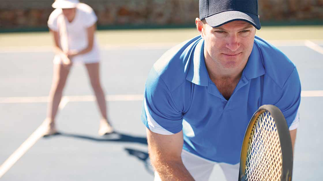 Image of two adults playing doubles tennis