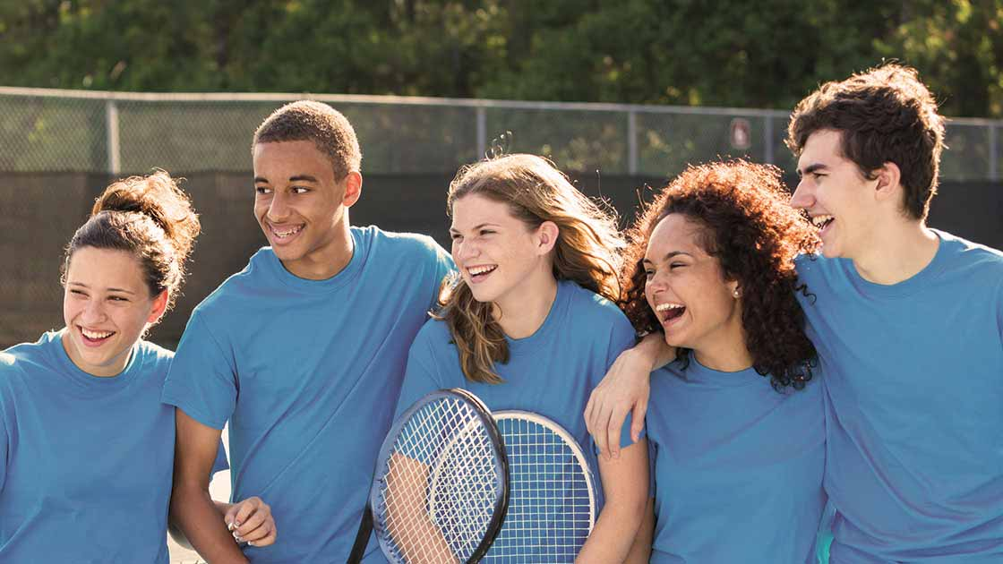 Image of five happy teens on a tennis court