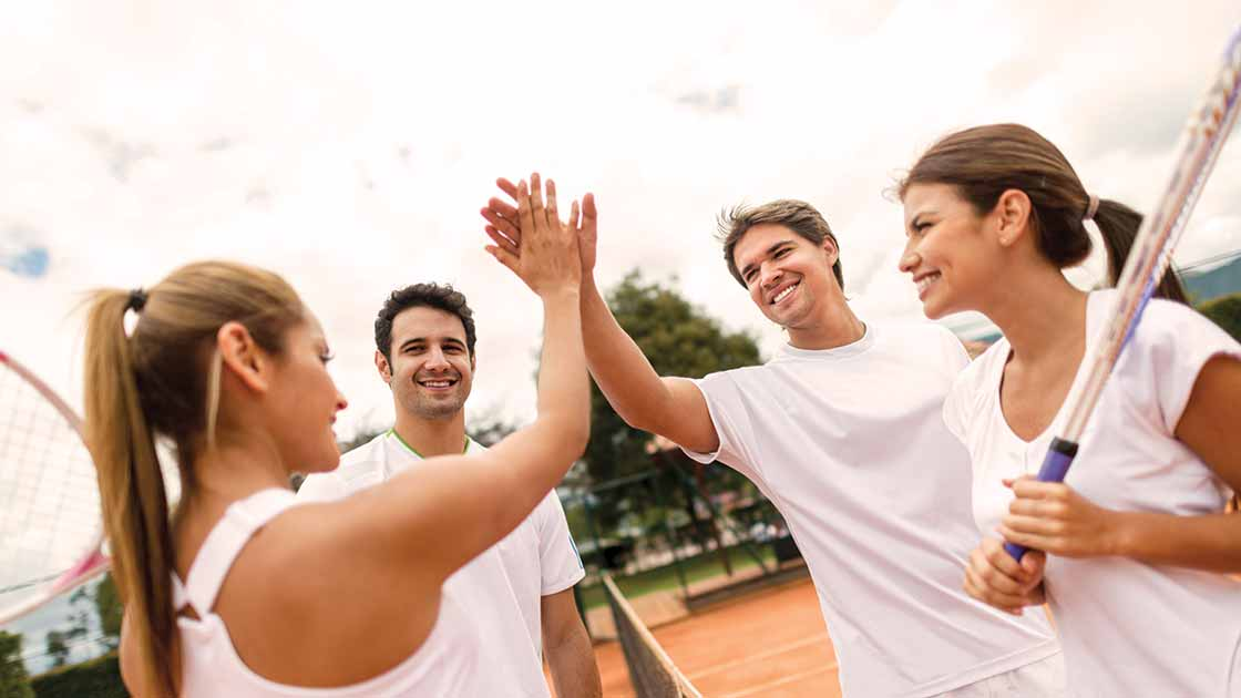 Image of four adults holding tennis rackets & high-fiving