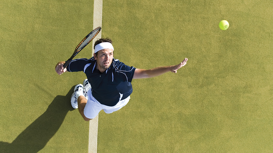 Image of a man jumping and swinging a tennis racket