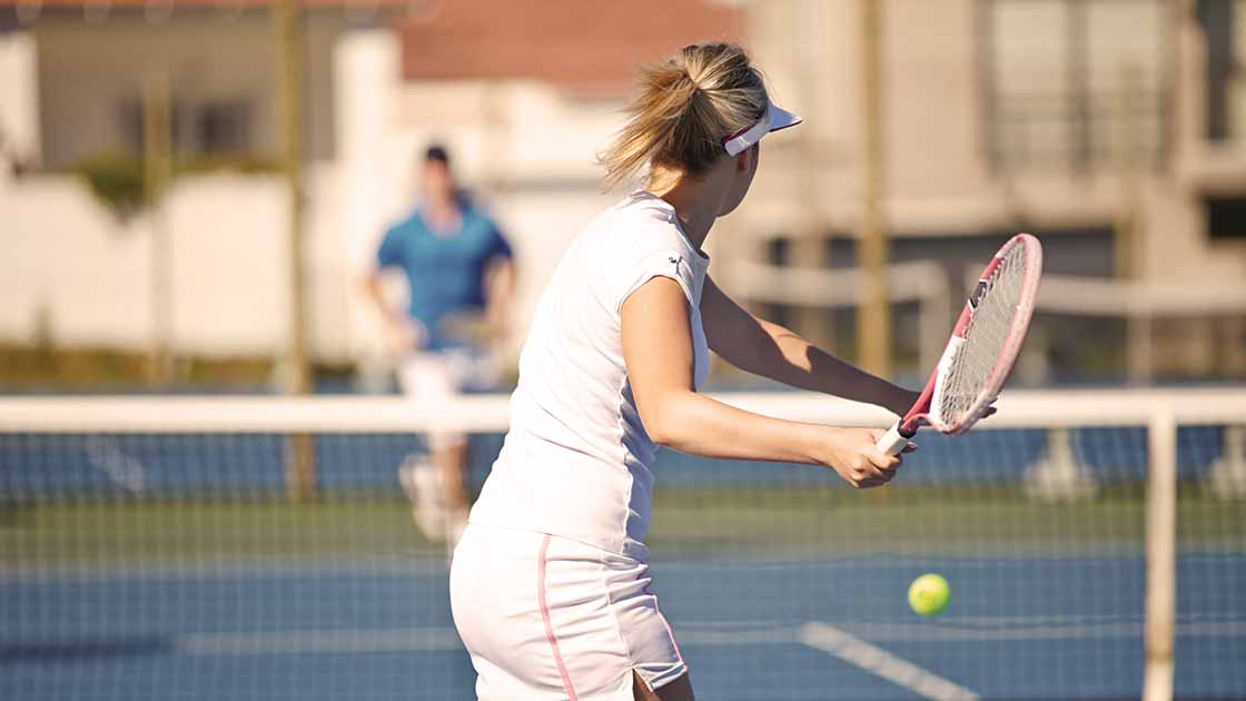 Image of a teen girl swinging a tennis racket at a ball