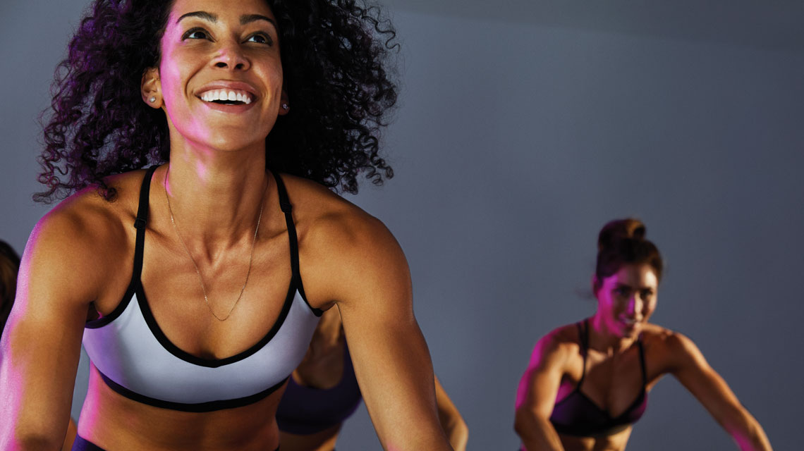 Two women in athletic clothing smiling in an indoor cycle class