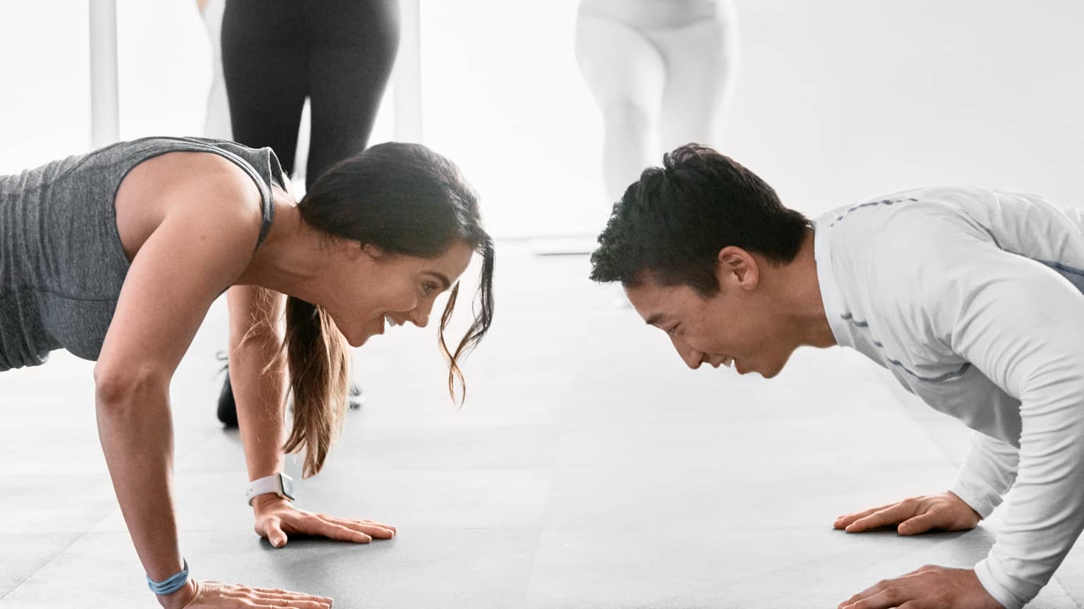 Two people in a group fitness class face each other while doing pushups