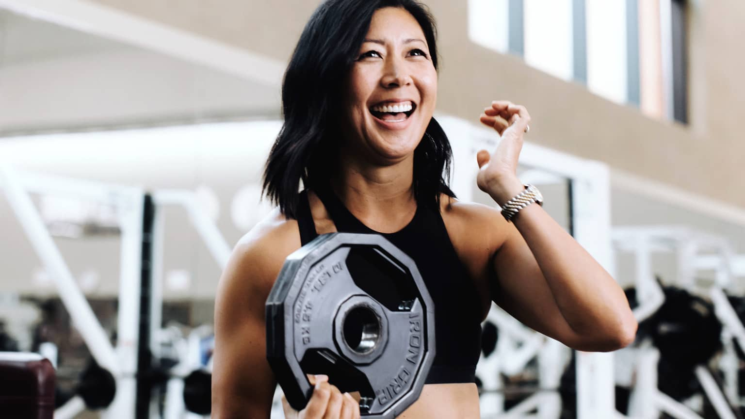 A smiling woman in workout clothes stands in front of a row of fitness equipment holding a weight plate