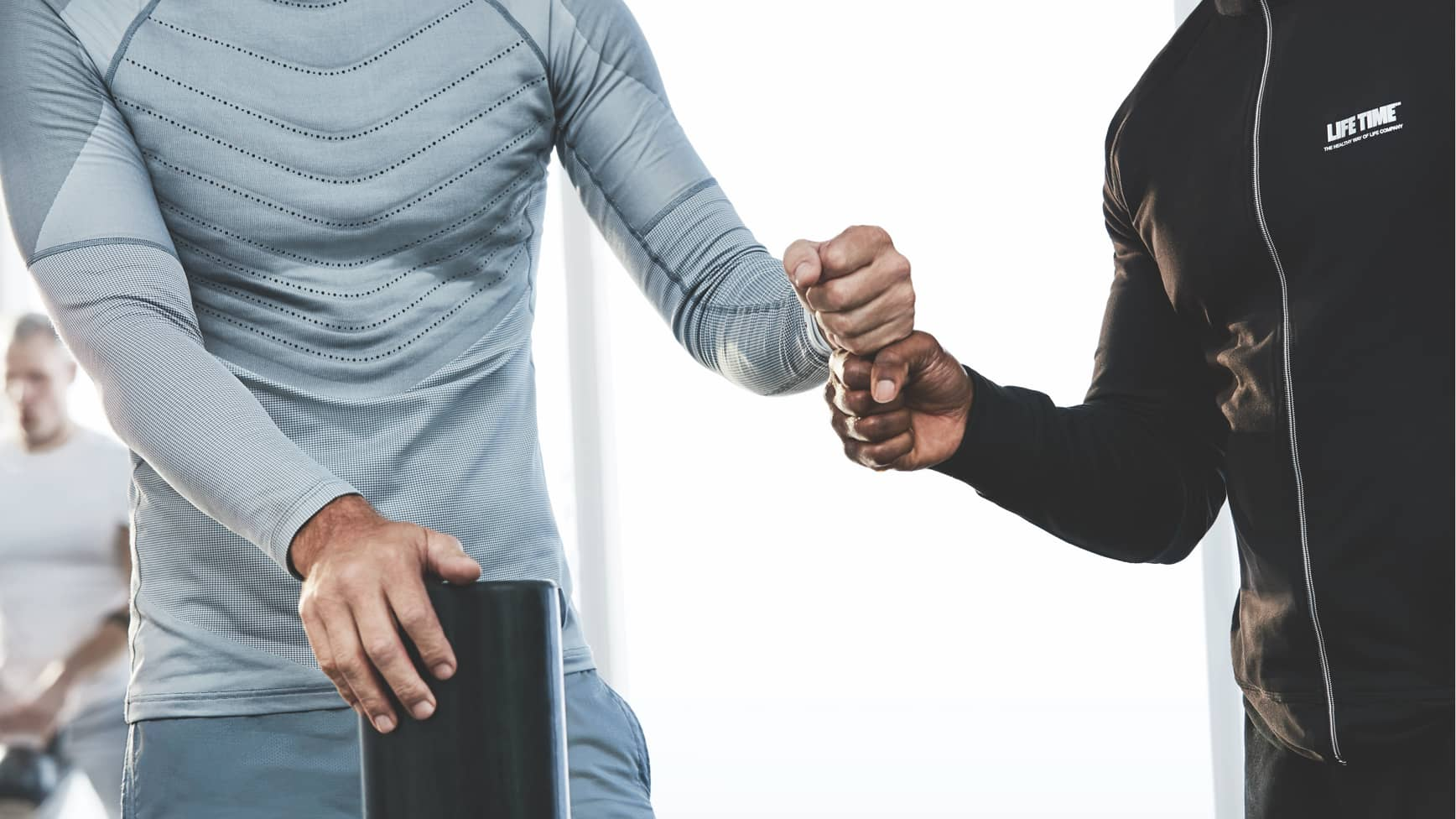 A trainer and his client share a fist bump during a workout