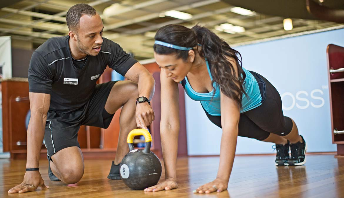 A Personal Training professional kneels next to a woman doing a plank