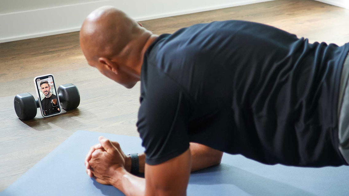 Fit male doing a plank while completing an at-home training session