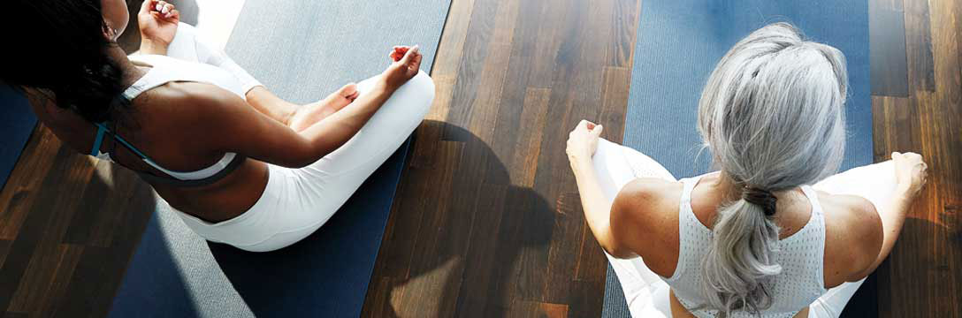 A woman meditating in a BE Yoga Class