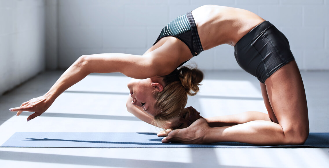 A woman performing a yoga backbend