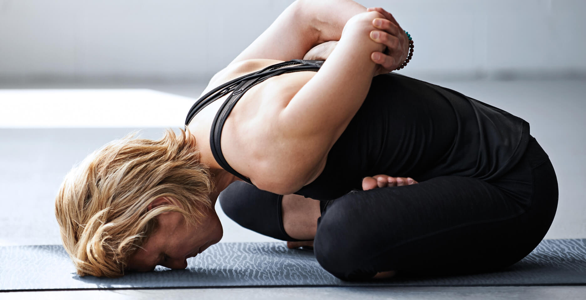 A woman practicing a flexible yoga move in a SURRENDER Yin Yoga Class