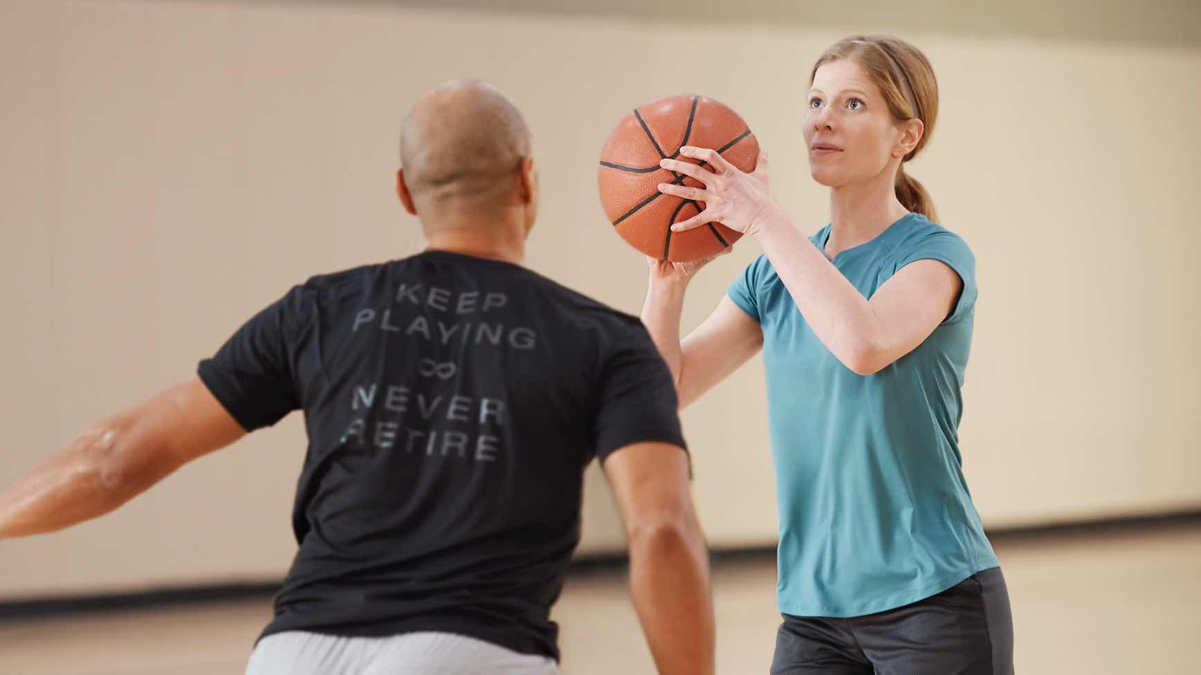 Woman shooting basketball with man guarding her